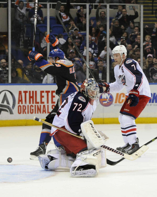New York Islanders' Travis Hamonic (3) celebrates his goal as Columbus Blue Jackets goalie Sergei Bobrovsky (72) and Jack Johnson (7) react in the second period of an NHL hockey game, Sunday, March 23, 2014, in Uniondale, N.Y. (AP Photo/Kathy Kmonicek)