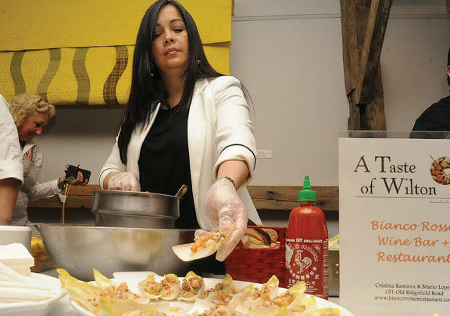 Cristina Ramierez, owner of Bianco Rosso Wine Bar & Restaurant in Wilton serves some favorites from the menu at the 2015 Taste of Wilton held at the Wilton Historical Society on Monday. Photo/Matthew Vinci