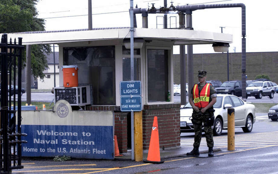 FILE - In this May 3, 2004 file photo, security personnel wait to inspect vehicles entering Norfolk Naval Station in Norfolk, Va. A sailor was fatally shot at the world's largest naval base late Monday, March 24, 2014, and security forces killed a male civilian suspect, base spokeswoman Terri Davis said. (AP Photo/The Virginian-Pilot, Mort Fryman)