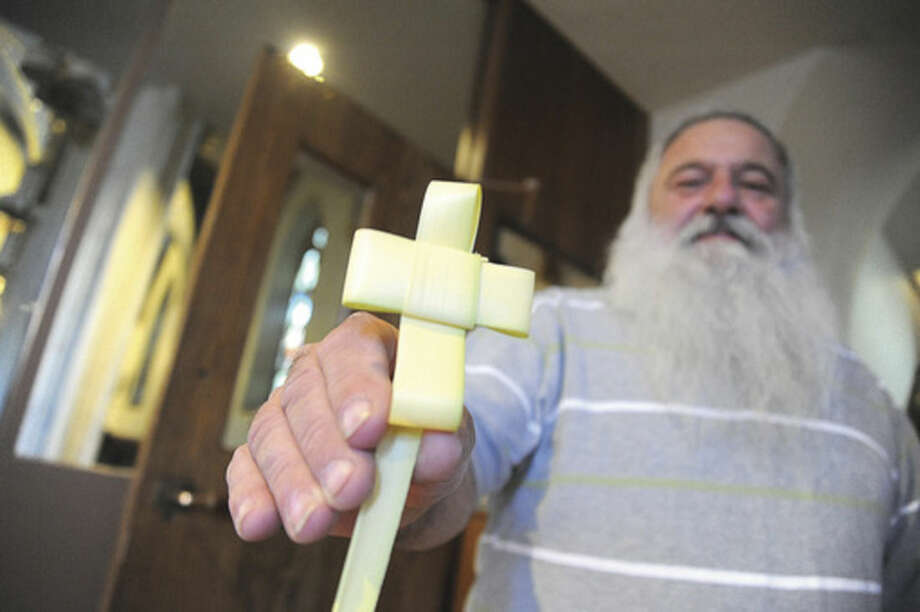 Joe Lorenti at the Palm Sunday Mass at St. Mary's Roman Catholic Church in Norwalk. Lorenti has been making crosses from palms since he was a child.