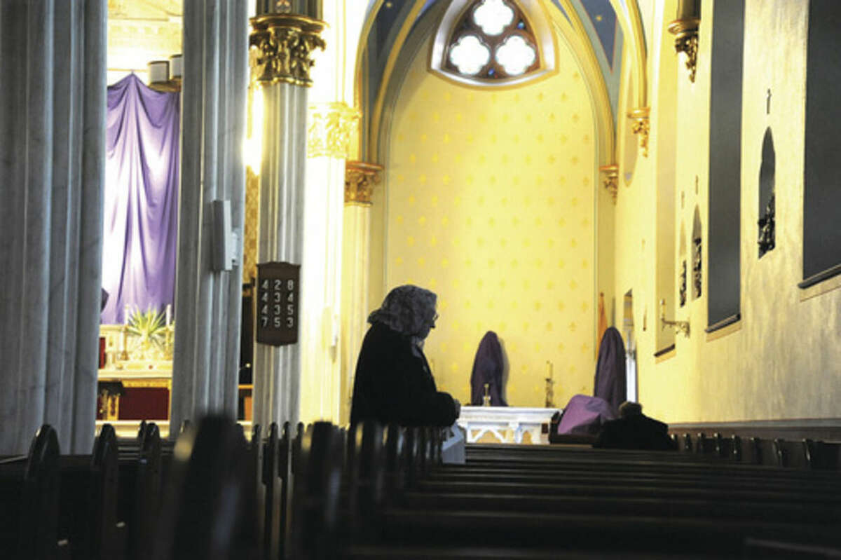 A member of St. Mary Church in Norwalk prays the staions of the cross at the Palm Sunday mass. Hour photo/Matthew Vinci