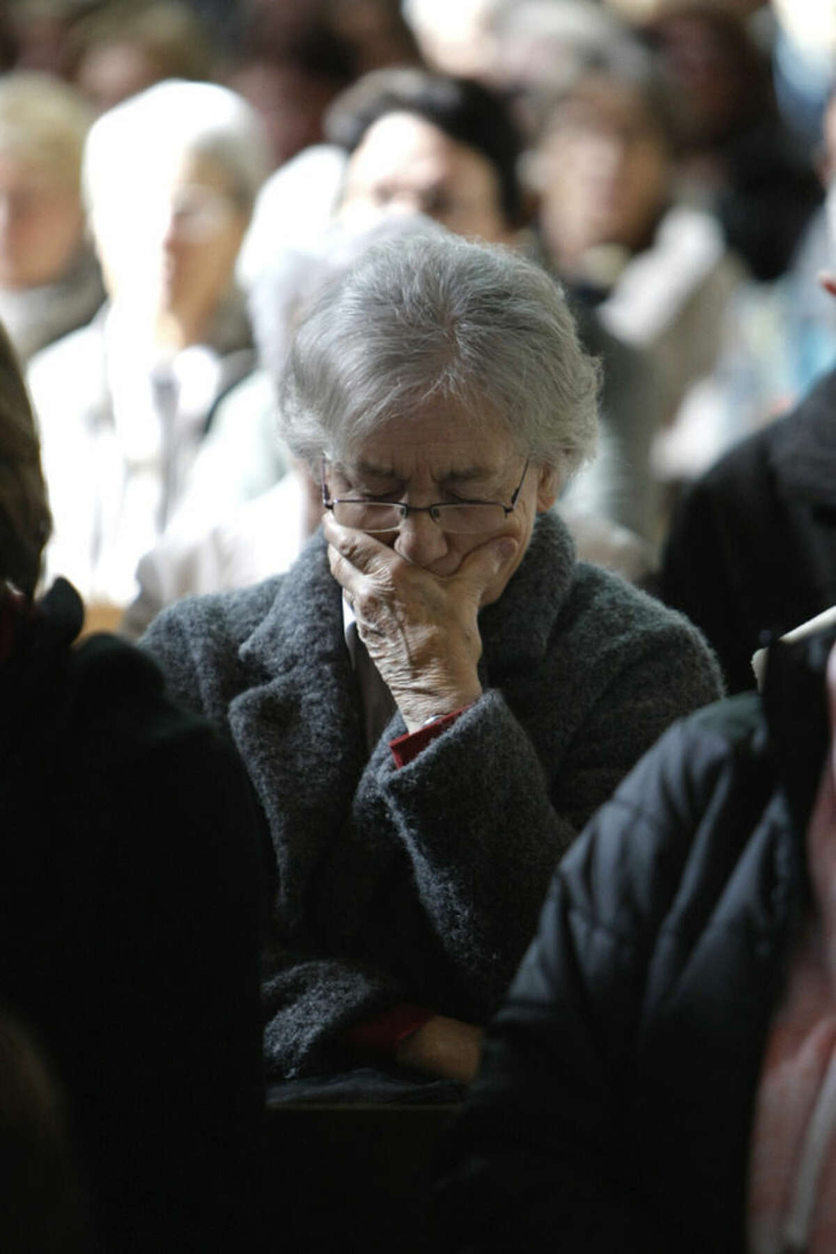 A woman looks down during the special Mass to honour the victims of the Germanwings jet crash, inside the cathedral Notre Dame de Bourg, in Digne-les-Bains, France, Saturday, March 28, 2015. French prosecutors say co-pilot Andreas Lubitz deliberately crashed the Germanwings flight into a mountain on Tuesday, killing all 150 people aboard. German prosecutors are trying to determine what caused Lubitz to take such a devastating decision. (AP Photo/Claude Paris)