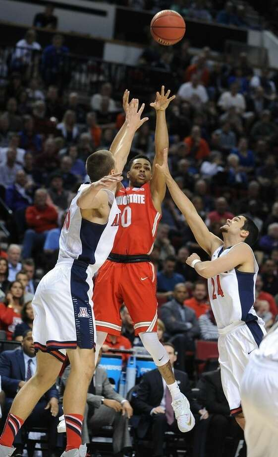 FILE - In this March 21, 2015, file photo, Ohio State guard D'Angelo Russell, center, shoots between Arizona guard Elliott Pitts, right, and Arizona center Kaleb Tarczewski during an NCAA college basketball tournament round of 32 game in Portland, Ore. Russell was selected to the AP All-America team, Monday, March 30, 2015. (AP Photo/Greg Wahl-Stephens, File)