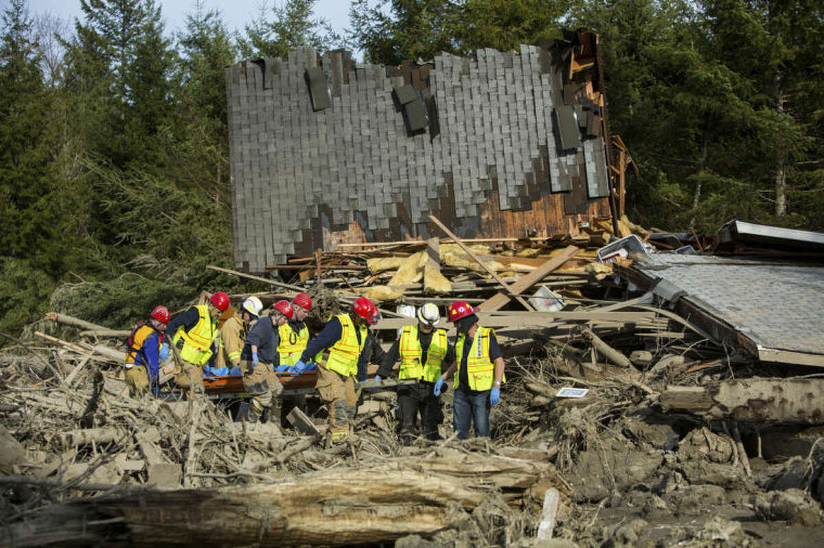 Rescue workers remove a body from the wreckage of homes destroyed by Saturday's mudslide near Oso, Wash, on Monday, March 24, 2014. The search for survivors of Saturday's deadly mudslide grew Monday to include scores of people who were still unaccounted for as the death toll from the wall of trees, rocks and debris that swept through the rural community rose to at least 14. (AP Photo/seattlepi.com, Joshua Trujillo)