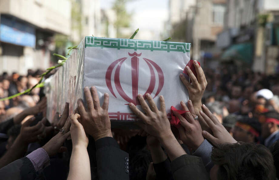 In this picture taken on Sunday, March 29, 2015, and released by the semi official Iranian Fars News Agency, a group of mourners carry the flag draped coffin of Ali Yazdani, a member of Iran's Revolutionary Guard, whom the Guard says has been killed during U.S. drone strike near the Iraqi city of Tikrit. Iran's Revolutionary Guard says a U.S. drone strike killed two of its advisers near the Iraqi city of Tikrit, though the U.S. said Monday its coalition conducted no airstrikes against the Islamic State group in the area during that time. (AP Photo/Fars News Agency, Mohammad Reza Jofar)