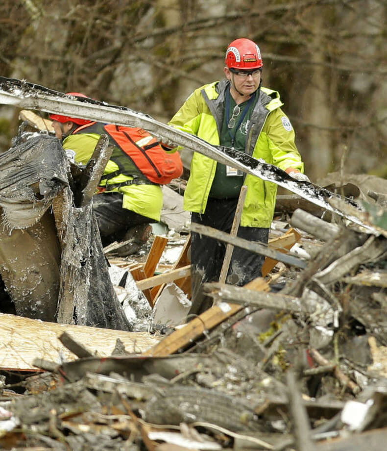 A search and rescue worker clears debris from a house Tuesday, March 25, 2014, on the western edge of the massive mudslide that struck near Arlington, Wash., on Saturday, killing at least 14 people and leaving dozens missing. (AP Photo/Ted S. Warren, Pool)