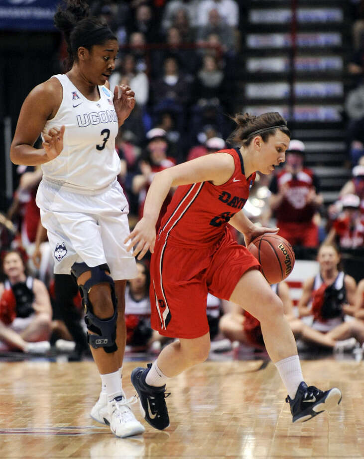 Dayton guard Andrea Hoover, right, dribbles past Connecticut forward Morgan Tuck (3) during the first half of a regional final game in the NCAA women's college basketball tournament on Monday, March 30, 2015, in Albany, N.Y. (AP Photo/Tim Roske)