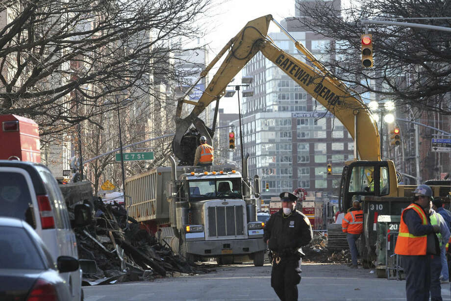 Rubble is moved Sunday, March 29, 2015, at the site of an apparent gas explosion that took place three days earlier in the East Village neighborhood of New York. (AP Photo/Tina Fineberg)