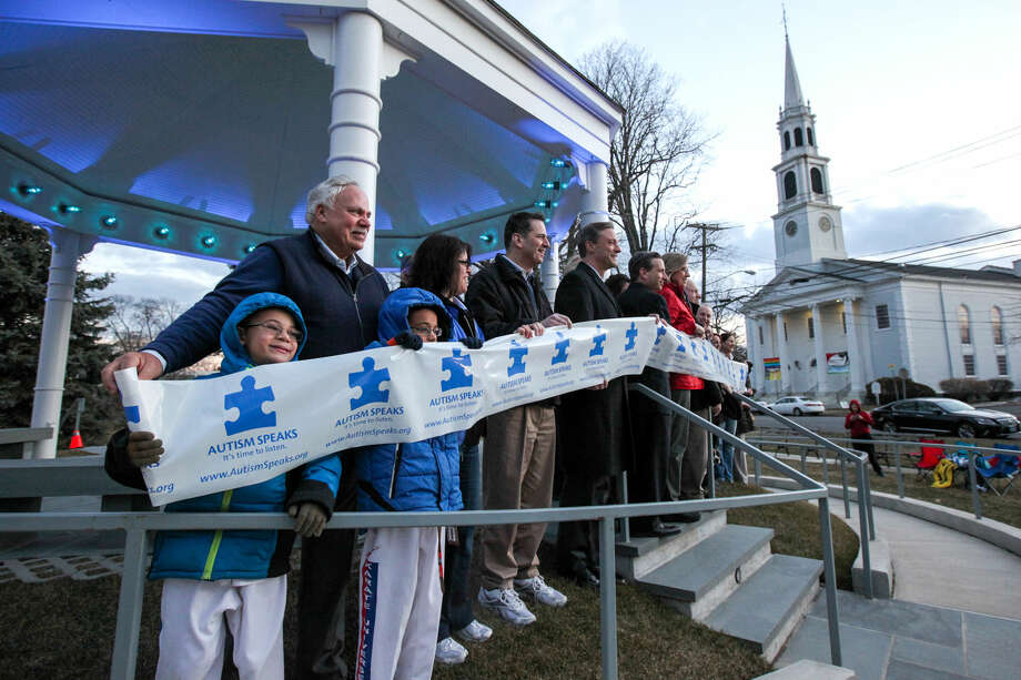 """Hour photo/Chris Palermo. Supporters and Norwalk dignitaries hold up the """"Autism Speaks"""" banner in recognition of April as Autism Aqarenes Month at the Norwalk Green Gazebo Monday night. The gazebo has been lit and will remain blue for the entire month of April."""