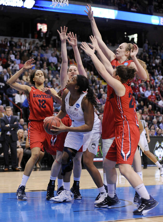 Connecticut forward Morgan Tuck (3) is guarded by Dayton players Jodie Cornelie-Sigmundova, of France (12), Kelley Austria, Ally Malott and Andrea Hoover during the second half of a regional final game in the NCAA women's college basketball tournament on Monday, March 30, 2015, in Albany, N.Y. UConn won 91-70. (AP Photo/Tim Roske)