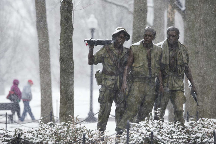 "Visitors walk past the ""The Three Soldiers"" statue that is part of the Vietnam Veterans Memorial during a snow storm in Washington, Tuesday, March 25, 2014. The calendar may say it's spring, but the mid-Atlantic region is seeing snow again. The National Weather Service has issued a winter weather advisories for much of the region Tuesday. The advisories warn that periods of snow could make travel difficult, with slippery roads and reduced visibility. (AP Photo/ Evan Vucci)"