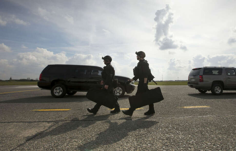 """Members of the US Secret Service's Counter Assault Team, known in the agency as CAT, walk across the tarmac at Kortrijk-Wevelgem International Airport, Wednesday, March 26, 2014 in in Waregem, Belgium. The Secret Service sent three agents home from the Netherlands just before Obama's arrival after one agent was found inebriated in an Amsterdam hotel, the Secret Service said Tuesday. The three agents were benched for """"disciplinary reasons,"""" said Secret Service spokesman Ed Donovan, declining to elaborate. Donovan said the incident was prior to Obama's arrival Monday in the country and did not compromise the president's security in any way. (AP Photo/Pablo Martinez Monsivais)"""