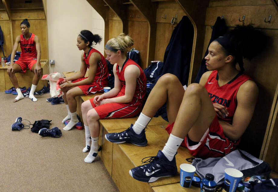 Dayton players sit in their locker room after their 91-70 loss to Connecticut in a regional final game in the NCAA women's college basketball tournament on Monday, March 30, 2015, in Albany, N.Y. (AP Photo/Tim Roske)