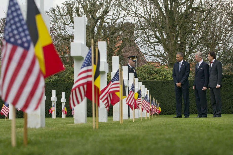 US President Barack Obama, third right, tours the American cemetery at Flanders Field with Belgian King Phillippe and Belgian Prime Minister Elio Di Rupo, far right, in Waregem, Belgium, Wednesday, March 26, 2014. President Barack Obama paid tribute to American troops who died a century ago in the struggle to save Europe in World War I. Obama laid a wreath at a memorial at Flanders Field in Belgium, where hundreds of fallen U.S. troops who helped liberate Belgium were buried. (AP Photo/Pablo Martinez Monsivais)