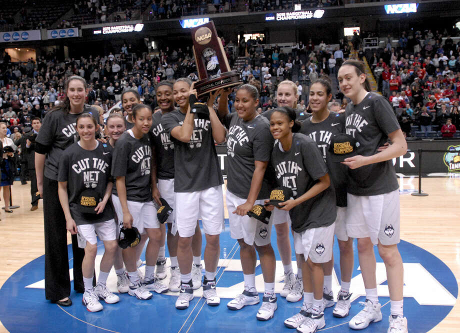 Connecticut players pose with the trophy after their 91-70 win over Dayton in a regional final game in the NCAA women's college basketball tournament Monday, March 30, 2015, in Albany, N.Y. (AP Photo/Tim Roske)