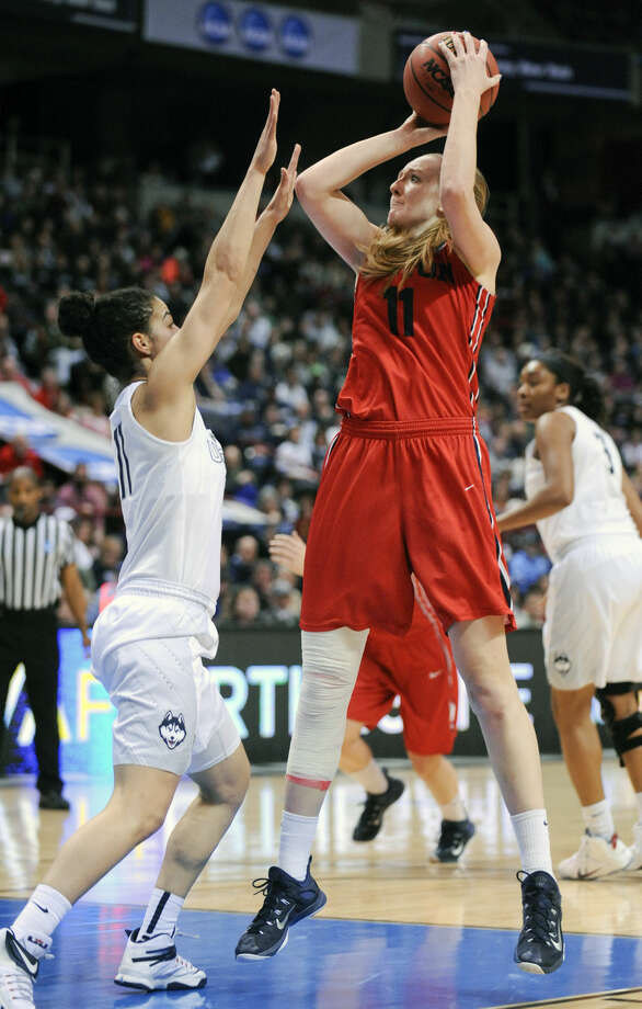 Dayton forward Ally Malott, right, shoots over Connecticut guard Kia Nurse during the first half of a regional final game in the NCAA women's college basketball tournament on Monday, March 30, 2015, in Albany, N.Y. (AP Photo/Tim Roske)