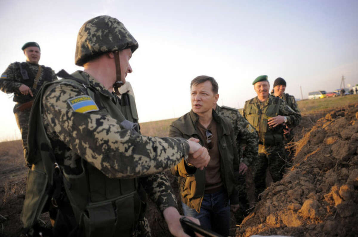 In this photo taken on Monday, March 24, 2014, Oleh Lyashko, center, a lawmaker, who supported the protests that ousted Russian-leaning president Viktor Yanukovych and his government, shakes hands with a soldier while visiting Ukrainian troops near Crimea, annexed by Russia, to support the Ukrainian soldiers?' spirit. Ukraine's government ordered Ukrainian troops to pull back Monday from Crimea, ending days of wavering as Russian forces stormed and seized bases on the peninsula.(AP Photo/Osman Karimov)