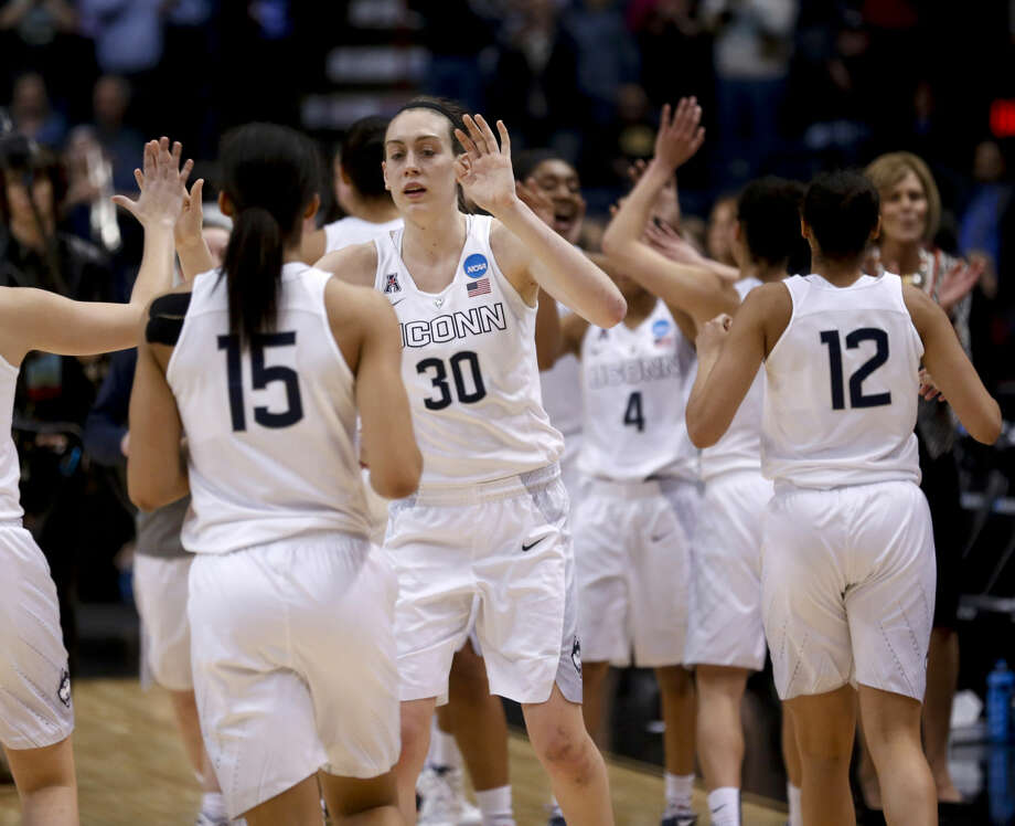 Connecticut's Breanna Stewart (30) and teammates celebrate their 91-70 win over Dayton during a regional final game in the NCAA women's college basketball tournament Monday, March 30, 2015, in Albany, N.Y. (AP Photo/Mike Groll)