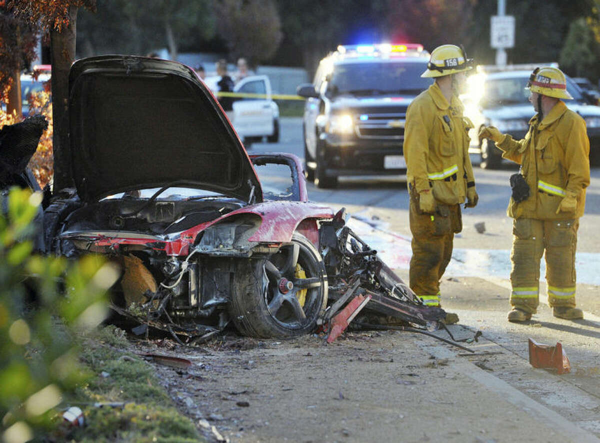 FILE - In this Saturday, Nov. 30, 2013, file photo, firefighters work next to the wreckage of a Porsche that crashed into a light pole killing actor Paul Walker and his Roger Rodas in Valencia, Calif. Crash investigators have determined that the Porsche was traveling approximately 90 mph when it lost control on a city street and smashed into a light pole, killing the actor and his friend. A person who has reviewed the investigators?' report told The Associated Press that it concluded unsafe driving, not mechanical problems, caused the crash. The person requested anonymity because the report has not been officially released yet. (AP Photo/The Santa Clarita Valley Signal, Dan Watson) LOS ANGELES DAILY NEWS OUT. MANDATORY CREDIT