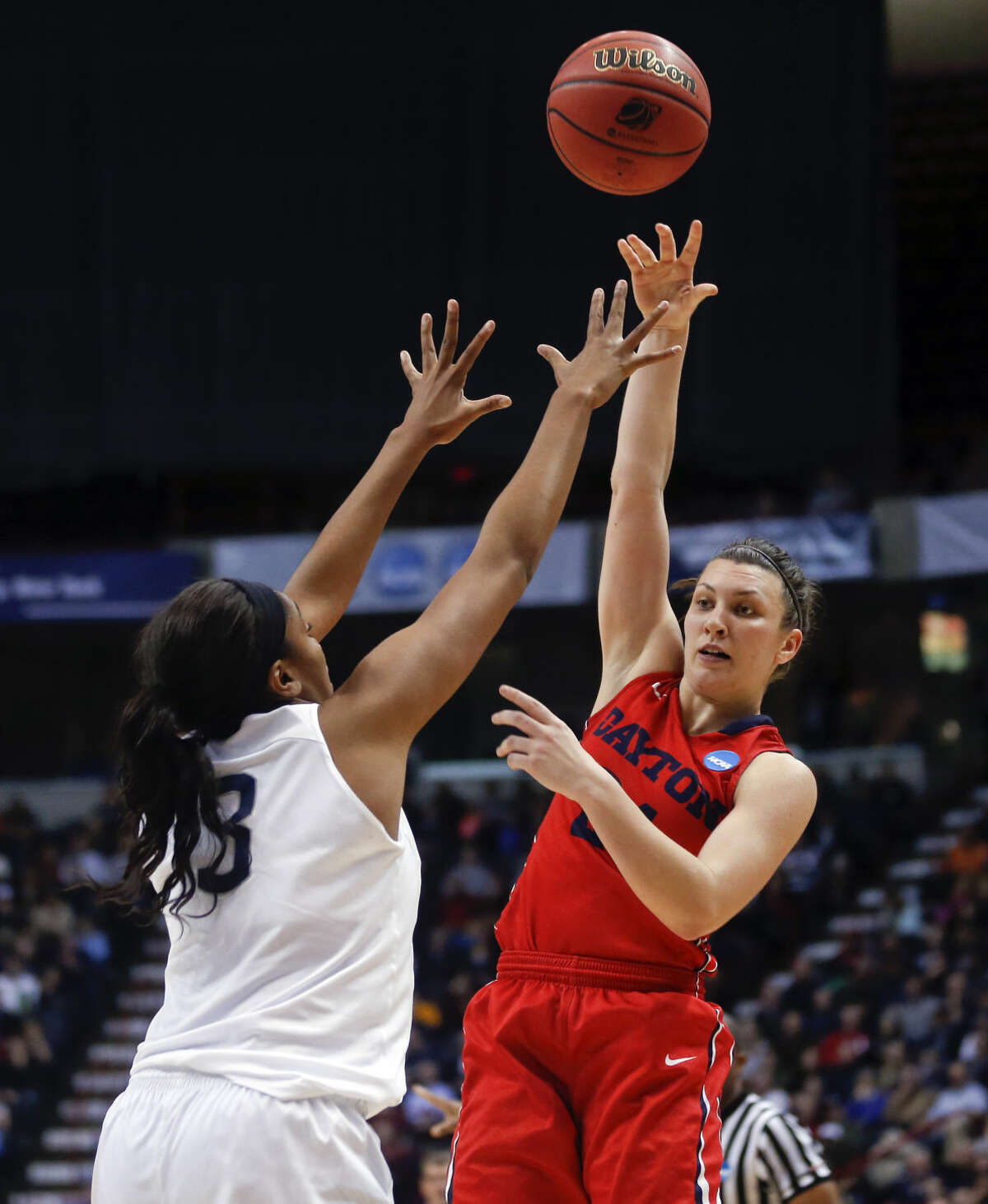 Dayton guard Andrea Hoover, right, passes over Connecticut forward Morgan Tuck during the second half of a regional final game in the NCAA women's college basketball tournament Monday, March 30, 2015, in Albany, N.Y. (AP Photo/Mike Groll)