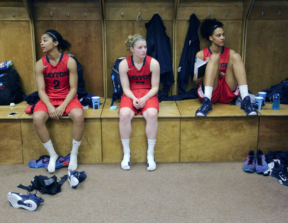 Dayton players Amber Deane, Jenna Burdette and Jodie Cornelie-Sigmundova, of France, sit in the team locker room after their 91-70 loss to Connecticut in a regional final game in the NCAA women's college basketball tournament on Monday, March 30, 2015, in Albany, N.Y. (AP Photo/Tim Roske)