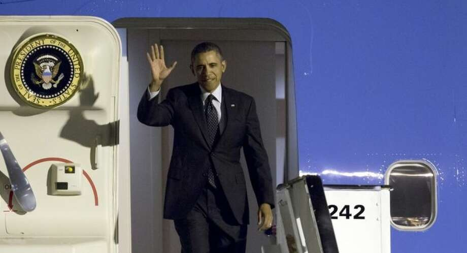 U.S. President Barack Obama waves as arrives from Air Force One at Zaventem airport in Brussels on Tuesday, March 25, 2014. Obama is on a one day visit to Belgium to meet with EU leaders and visit the WWI Flanders Fields American Cemetery. (AP Photo/Virginia Mayo)