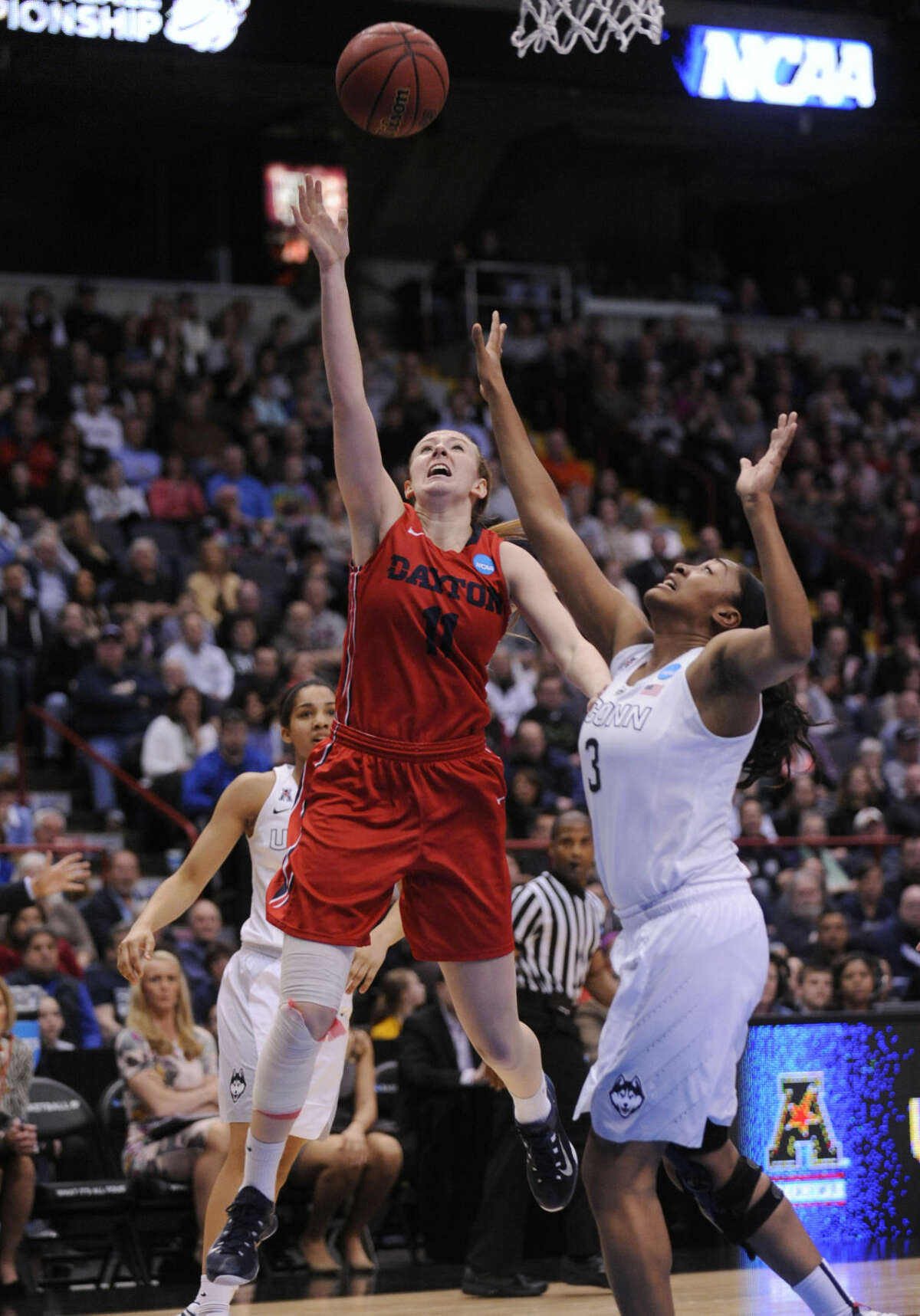 Dayton forward Ally Malott (11) shoots over Connecticut forward Morgan Tuck (3) during the first half of a regional final game in the NCAA women's college basketball tournament Monday, March 30, 2015, in Albany, N.Y. (AP Photo/Tim Roske)