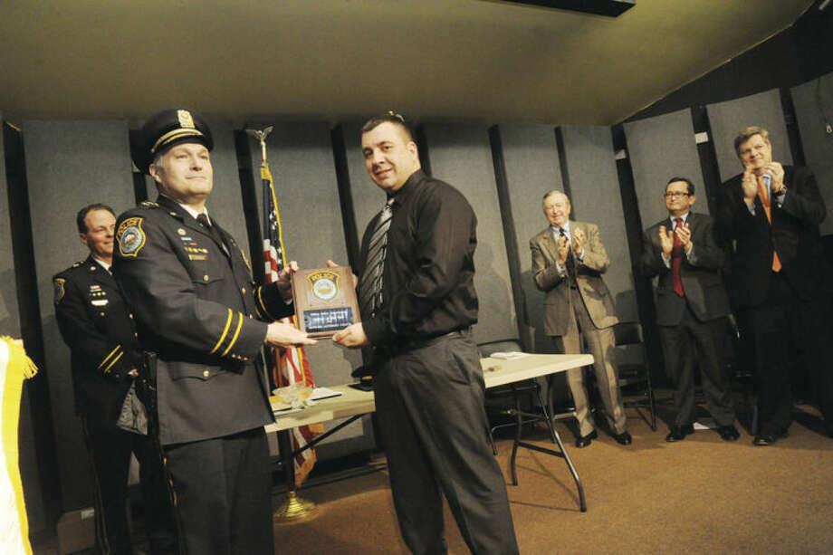 Officer Anthony Cocco is presented the Officer of the Year award Monday by police Chief Michael Lombardo at the Trackside Teen Center in Wilton.