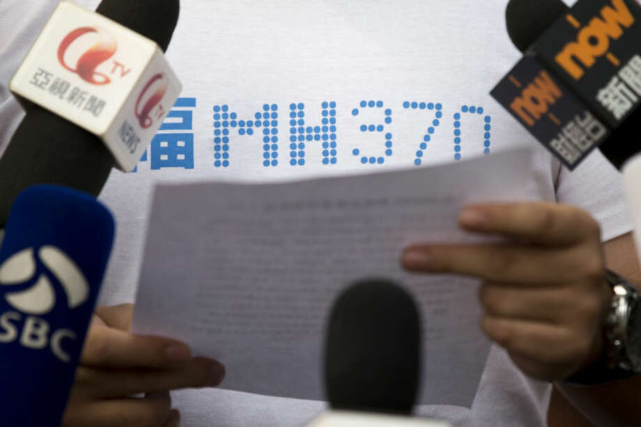 A representative of relatives of Chinese passengers onboard Malaysia Airlines Flight 370, center, makes an announcement to journalists prior to a briefing with Malaysian officials at a hotel in Beijing, China, Wednesday, March 26, 2014. About two-thirds of the missing, 239 people onboard, are Chinese, and their relatives have lashed out at Malaysia for essentially declaring their family members dead without any physical evidence of the plane's remains. (AP Photo/Alexander F. Yuan)