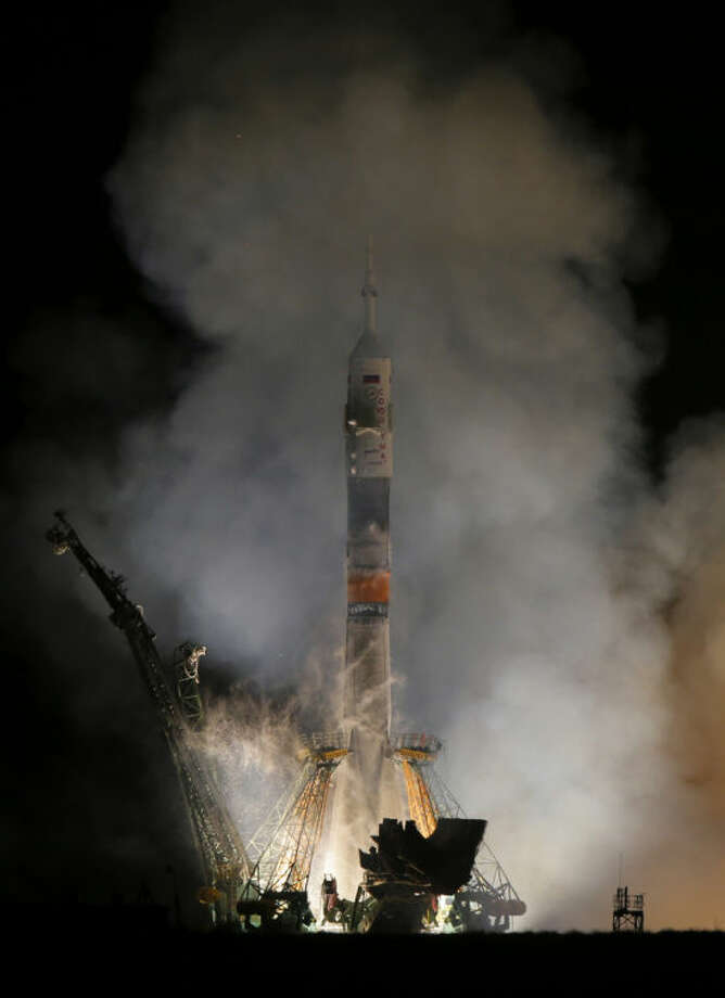 The Soyuz-FG rocket booster with Soyuz TMA-12M space ship carrying a new crew to the International Space Station (ISS) blasts off at the Russian leased Baikonur cosmodrome, Kazakhstan, Wednesday, March 26, 2014. The Russian rocket carries astronaut Steven Swanson, Russian cosmonauts Alexander Skvortsov and Oleg Artemyev. (AP Photo/Dmitry Lovetsky)