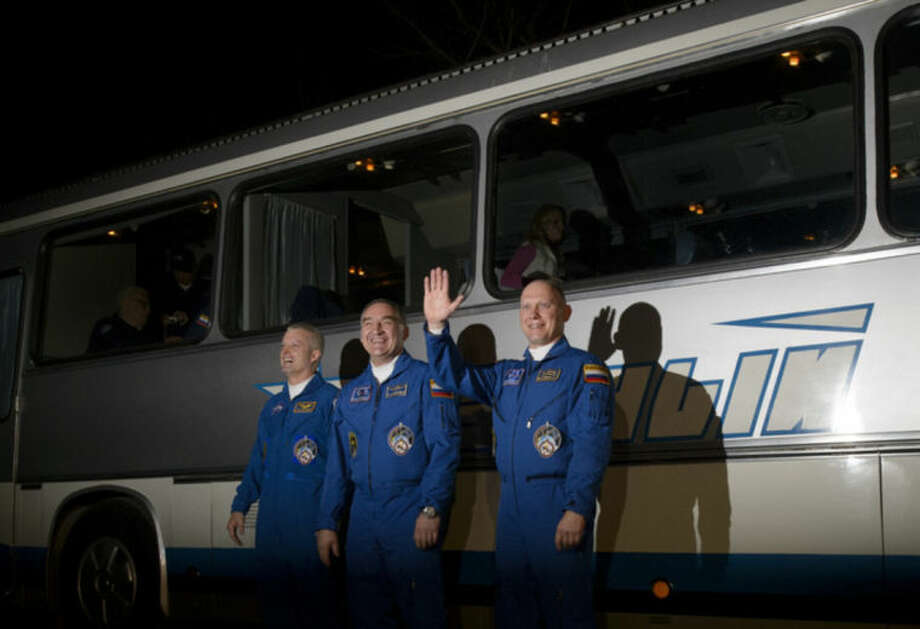 In this image released by NASA, from left, Expedition 39 flight engineer Steven Swanson of NASA, Soyuz commander Aleksander Skvortsov, of the Russian Federal Space Agency (Roscosmos), and flight engineer Oleg Artemyev of Roscosmos, wave as they depart the Cosmonaut Hotel Tuesday, March 25, 2014, in Baikonur, Kazakhstan. The mission is set to launch March 26 from the Baikonur Cosmodrome. (AP Photo/NASA, Joel Kowsky) MANDATORY CREDIT
