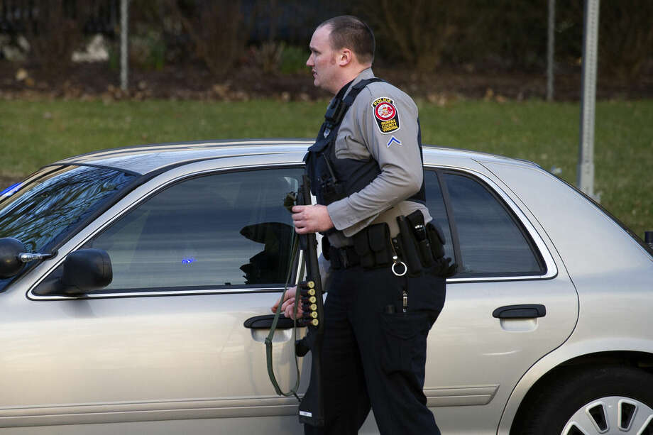 A Fairfax County, Va. Police officer with a shotgun stands outside of Inova Fairfax Hospital Center in Falls Church, Va., Tuesday, March 31, 2015, where a prisoner broke free from his security guard and took his gun. One shot was fired early Tuesday as a guard wrestled with a prisoner, who then fled a northern Virginia hospital with a gun setting off a lockdown and search, police said. (AP Photo/Cliff Owen)