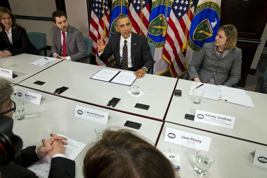 FILE - In this March 19, 2015, file photo, President Barack Obama, flanked by senior adviser Brian Deese, left, and Christina Goldfuss, managing director of the Council on Environmental Quality, speaks at Energy Department in Washington. In a highly anticipated announcement, the United States will pledge to cut its greenhouse gas emissions by up to 28 percent as its contribution to a major global climate treaty nearing the final stages of negotiation, according to people briefed on the White House's plans. (AP Photo/Jacquelyn Martin)