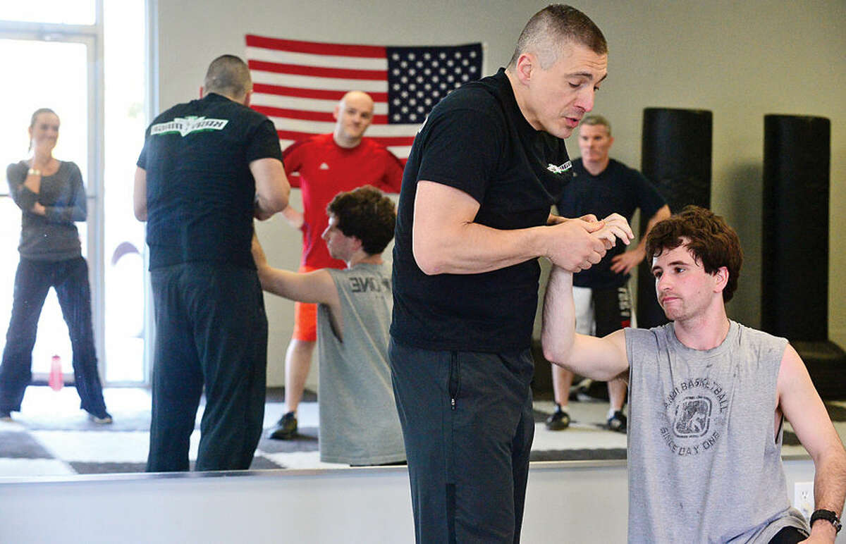 Hour photo / Erik Trautmann Gus Bottazzi, Chief Instructor and owner of Israeli Krav Maga-CT, brings down student Kenny Simeone, during a lesson the Main Ave gym Tuesday. Krav Maga (