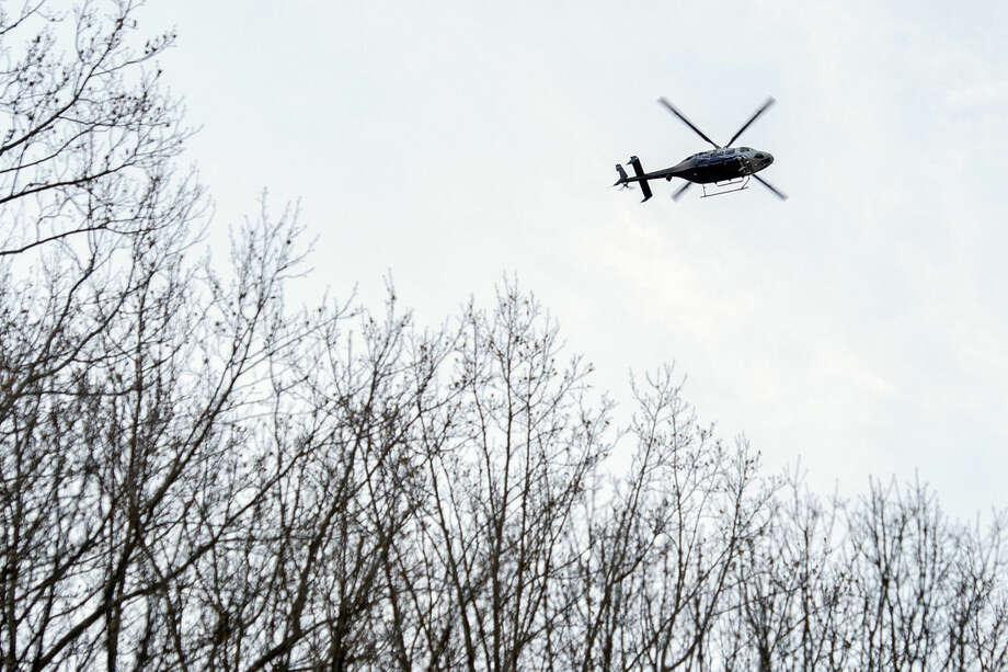 A police helicopter flies near Inova Fairfax Hospital Center in Falls Church, Va., Tuesday, March 31, 2015, where a prisoner broke free from his security guard and took his gun. One shot was fired early Tuesday as a guard wrestled with a prisoner, who then fled a northern Virginia hospital with a gun setting off a lockdown and search, police said. (AP Photo/Cliff Owen)