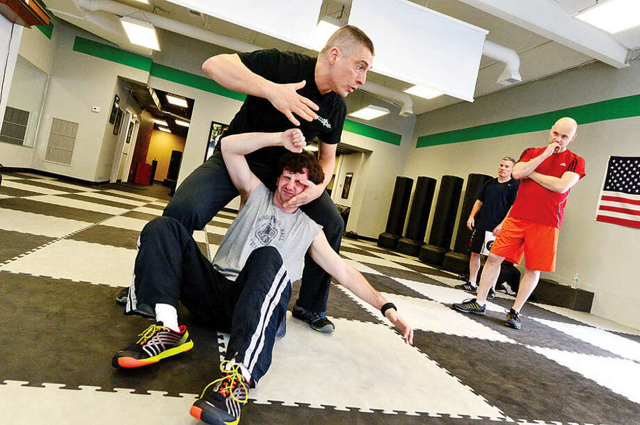 "Hour photo / Erik Trautmann Gus Bottazzi, Chief Instructor and owner of Israeli Krav Maga-CT, brings down student Kenny Simeone, during a lesson Tuesday. Krav Maga (""contact combat"") is the official self-defense system of the Israeli Defense Forces, Israeli National Police, and security services. Krav Maga is a superior, world-renowned self-defense and combat fitness training method to achieve top physical shape while learning real self-defense and fighting techniques."