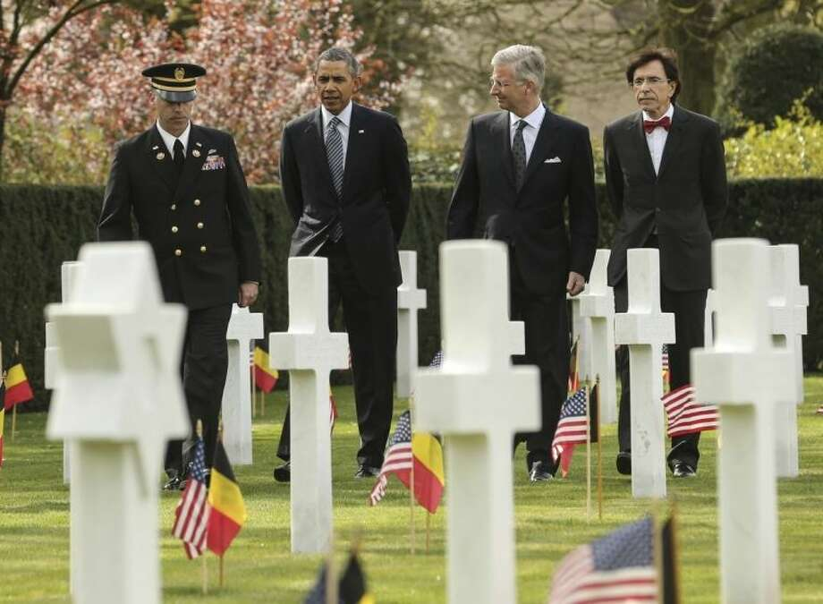 U.S. President Barack Obama, second left, walks among gravestones of World War One soldiers with Belgium's King Philippe, second right, and Belgian Prime Minister Elio Di Rupo, right, at the World War One Flanders Field American Cemetery in Waregem, Belgium on Wednesday, March 26, 2014. The cemetery contains the remains of 368 U.S. WWI military and support personnel. Of those remains, 21 are unknown and could not be identified. (AP Photo/Olivier Hoslet, Pool)
