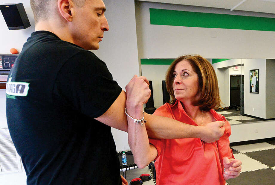 """Hour photo / Erik Trautmann Hour reporter Leslie Lake looks to takes down Gus Bottazzi, Chief Instructor and owner of Israeli Krav Maga-CT, during a lesson at his gym Tuesday. Krav Maga (""""contact combat"""") is the official self-defense system of the Israeli Defense Forces, Israeli National Police, and security services. Krav Maga is a superior, world-renowned self-defense and combat fitness training method to achieve top physical shape while learning real self-defense and fighting techniques."""