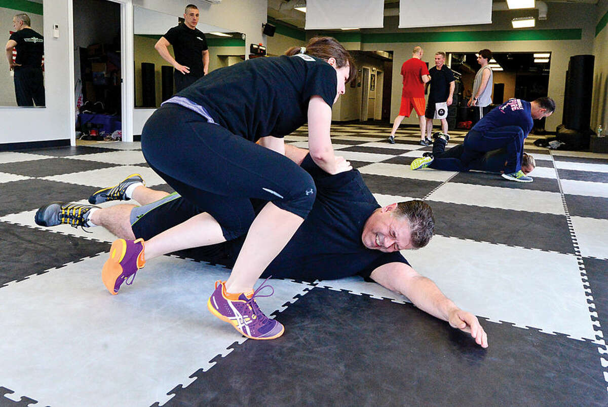 """Hour photo / Erik Trautmann Susan MacKenzie takes down Artie Kassimis Tuesday during a workout at Israeli Krav Maga-CT Tuesday. Krav Maga (""""contact combat"""") is the official self-defense system of the Israeli Defense Forces, Israeli National Police, and security services. Krav Maga is a superior, world-renowned self-defense and combat fitness training method to achieve top physical shape while learning real self-defense and fighting techniques."""