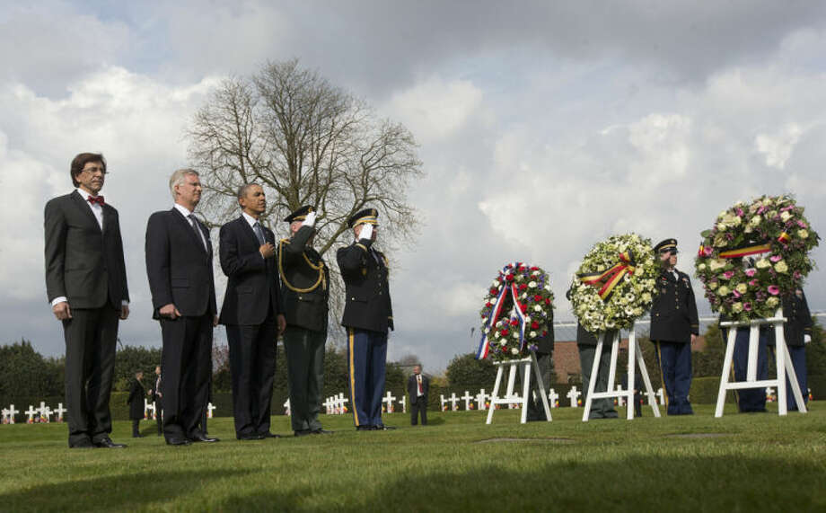 US President Barack Obama, center, at the wreath-laying ceremony with Belgian King Phillipe, and Belgian Prime Minister Elio Di Rupo, far left, at Flanders Field America Cemetery in Waregem, Belgium, Wednesday, March 26, 2014. President Barack Obama paid tribute to American troops who died a century ago in the struggle to save Europe in World War I. Obama laid a wreath at a memorial at Flanders Field in Belgium, where hundreds of fallen U.S. troops who helped liberate Belgium were buried. (AP Photo/Pablo Martinez Monsivais)