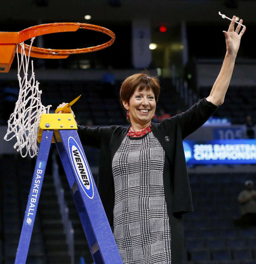 Notre Dame coach Muffet McGraw holds up part of the net after Notre Dame defeated Baylor 77-68 in a regional final in the NCAA women's college basketball tournament, Sunday, March 29, 2015, in Oklahoma City. (AP Photo/Sue Ogrocki)