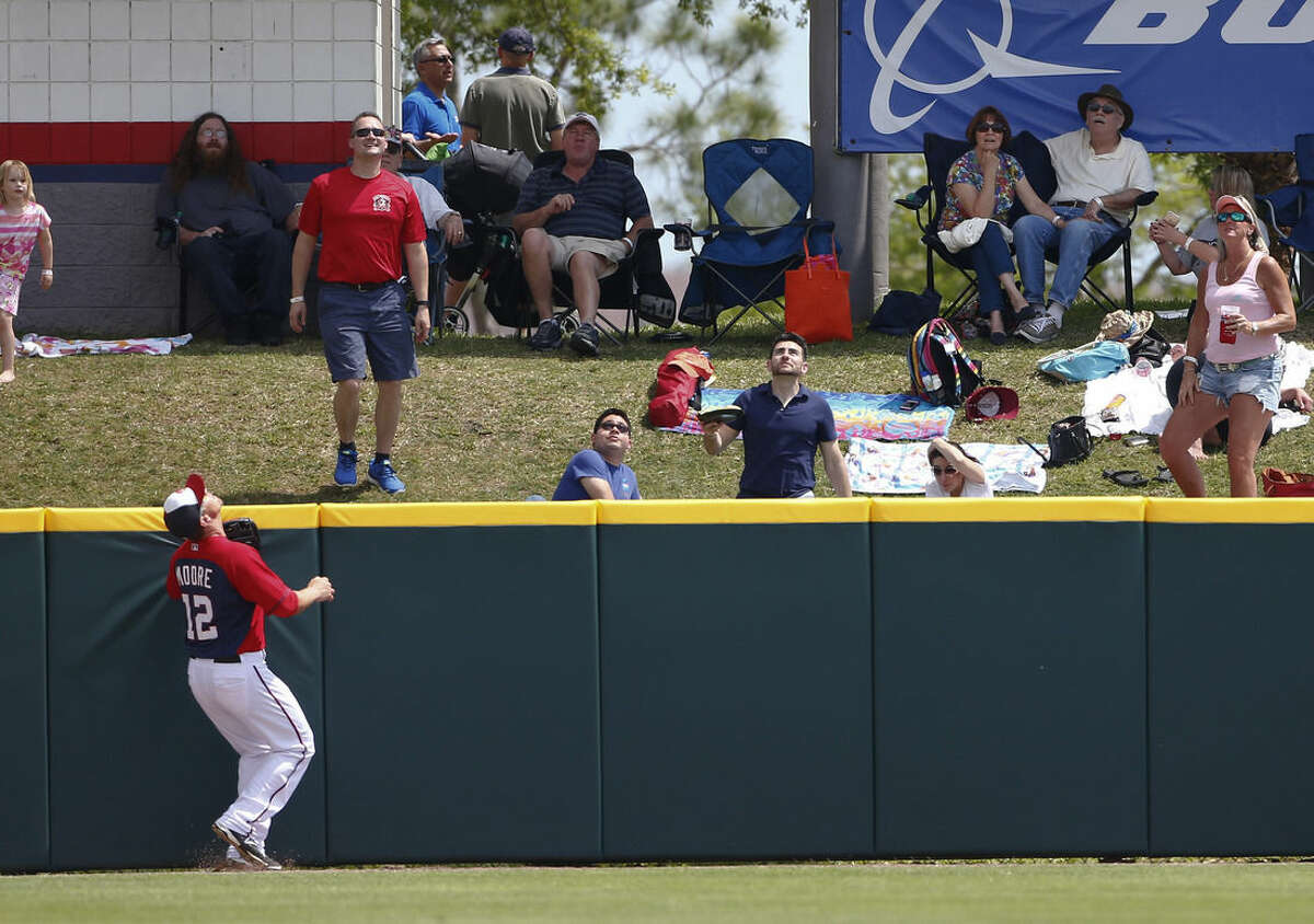 Washington Nationals first baseman Tyler Moore (12) watches a home run by New York Mets' John Mayberry Jr. (44) clear the fence in the sixth inning of an exhibition spring training baseball game Tuesday, March 31, 2015, in Viera , Fla. New York won 2-0. (AP Photo/John Bazemore)