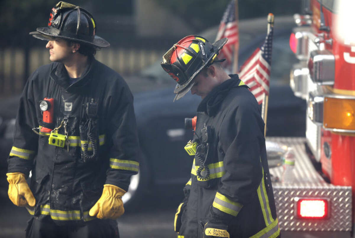A firefighter, right, lowers his head at the scene of a multi-alarm fire at a four-story brownstone in the Back Bay neighborhood near the Charles River, Wednesday, March 26, 2014, in Boston. (AP Photo/Steven Senne)