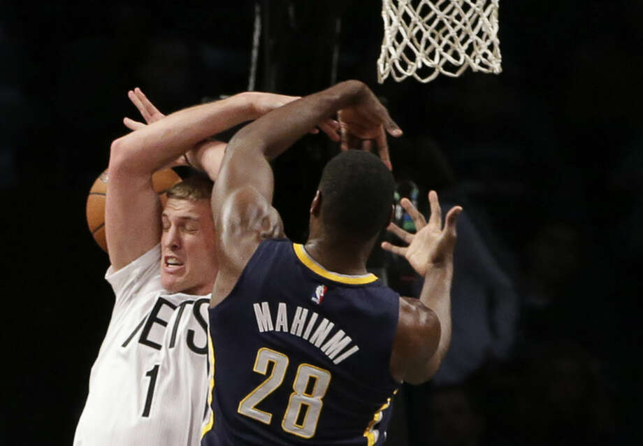 Indiana Pacers center Ian Mahinmi (28) knocks the ball from Brooklyn Nets center Mason Plumlee (1) in the first half of an NBA basketball game at the Barclays Center, Tuesday, March 31, 2015, in New York. (AP Photo/Kathy Willens)