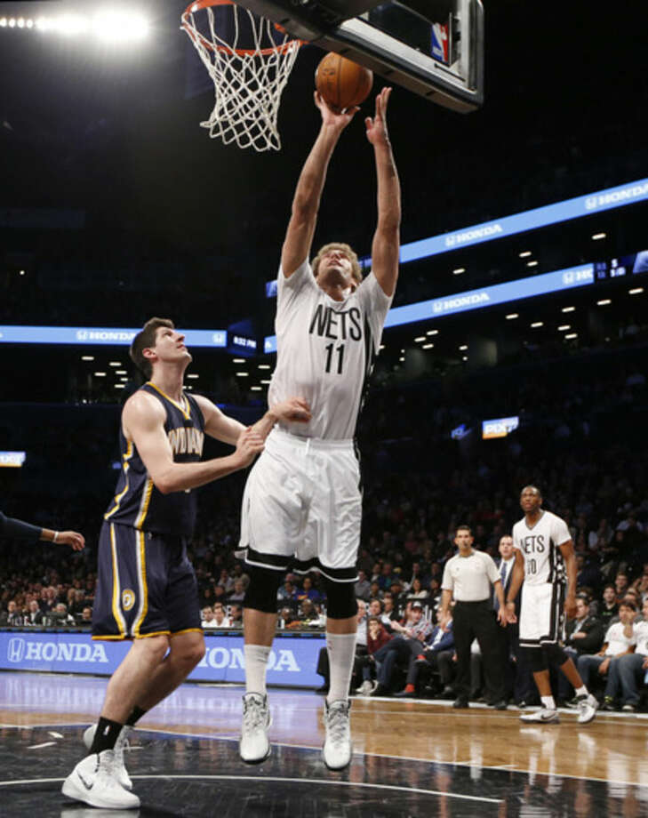Brooklyn Nets center Brook Lopez (11) shoots over Indiana Pacers forward Damjan Rudez (9) in the first half of an NBA basketball game at the Barclays Center, Tuesday, March 31, 2015, in New York. (AP Photo/Kathy Willens)
