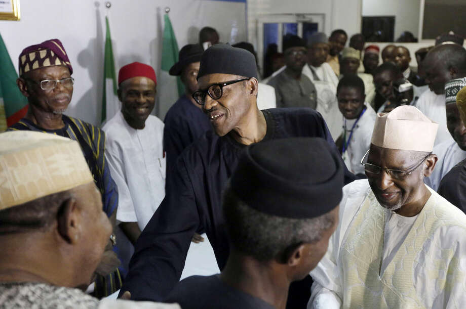 Nigerian former Gen. Muhammadu Buhari, center, shakes hands with party officials after speaking to journalists in Abuja, Nigeria, Wednesday, April 1, 2015. Nigerian President Goodluck Jonathan conceded defeat to Buhari, a 72-year-old former military dictator, who was elected in a historic transfer of power following the nation's most hotly contested election ever. (AP Photo/Sunday Alamba)