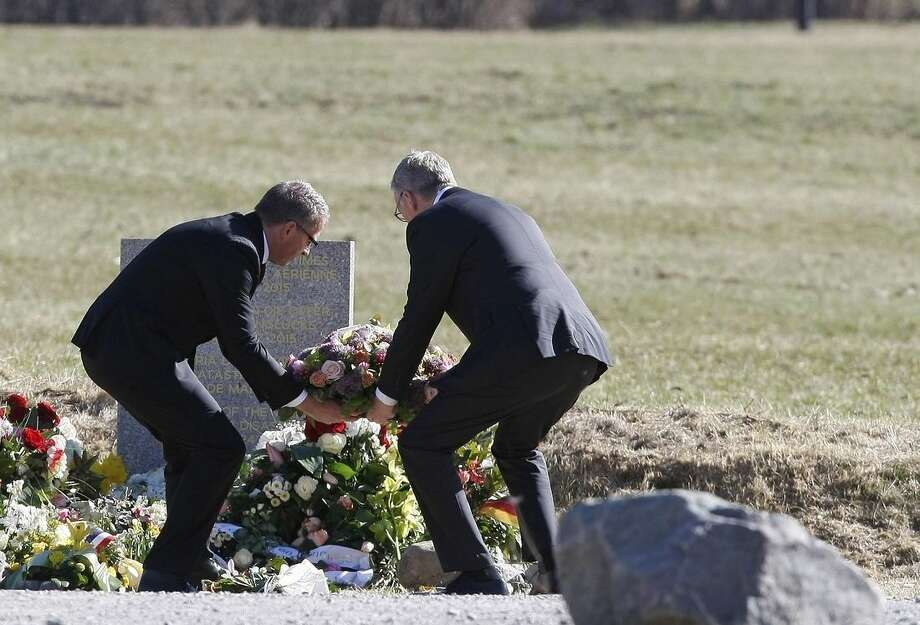 CEO of Germanwings Thomas Winkelmann and Lufthansa CEO Carsten Spohr, left, lay a wreath of flowers at a stone slab erected as a monument in memory of the victims, near the site of the Germanwings jet crash, in Le Vernet, France, Wednesday, April 1, 2015. The heads of Lufthansa and its low-cost airline Germanwings are visiting the site of the crash that killed 150 people amid mounting questions about the co-pilot and how much his employers knew about his mental health. (AP Photo/Claude Paris)