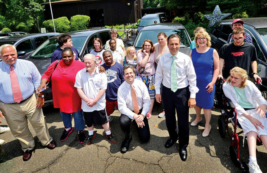Hour photo / Erik Trautmann State Representative Chris Perone, State Senator Bob Duff, join STAR Inc. Executive Director Katie Banzhaf, STAR staff and clients to help celebrate the purchase of 14 new vans made possible through Governor Malloy's Nonprofit Grant Program during a brief press conference Tuesday.