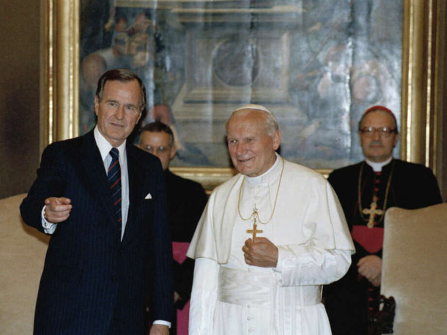 FILE - In this May 27, 1989, file photo, President George Bush, Sr. gestures while standing with Pope John Paul II in the papal library at the Vatican. President Obama is scheduled to meet Pope Francis for the first time on Thursday, March 27, 2014, at the Vatican. (AP Photo/Ron Edmonds, File)