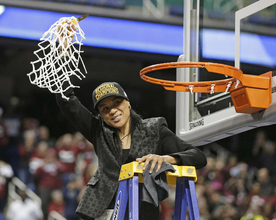 South Carolina head coach Dawn Staley waves the net to fans after a women's college basketball regional final game against Florida State in the NCAA Tournament in Greensboro, N.C., Sunday, March 29, 2015. South Carolina won 80-74. (AP Photo/Chuck Burton)